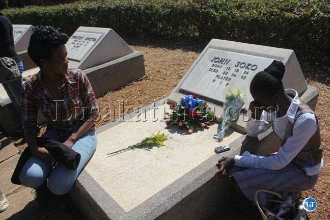 Serah Soko on the graveyard of her father John Soko while Suzyo Chibuye is looking on
