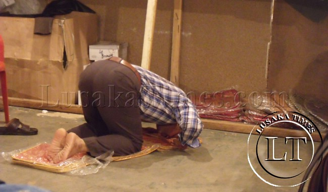 An Iranian exhibitor bows towards Mecca and prays after conducting business at the Trade fair in Ndola.