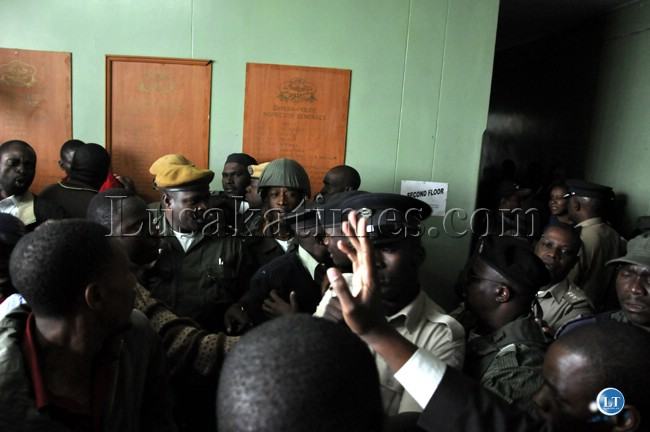 Police and UPND cadres push each other on the second floor of the Lusaka Central Police Station.
