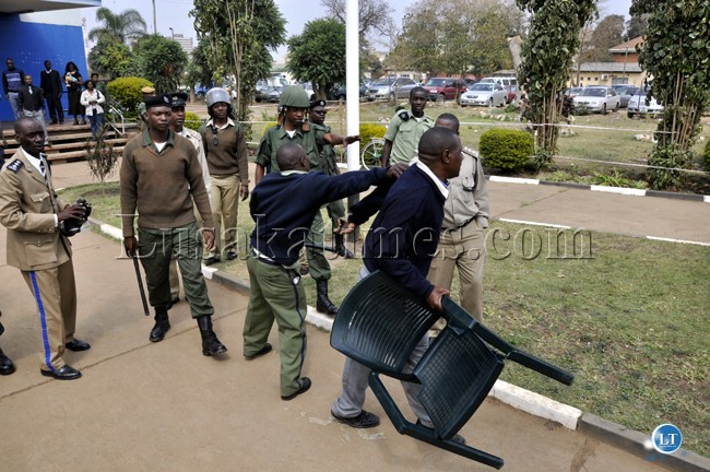 Police officers manhandle a UPND cadre who had carried the chair for party president Hakainde Hichilema