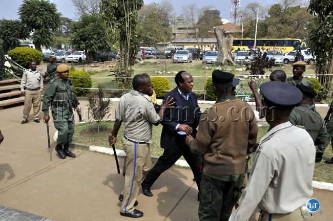 Police officers push a senior UPND official out of the Lusaka Central Police Station