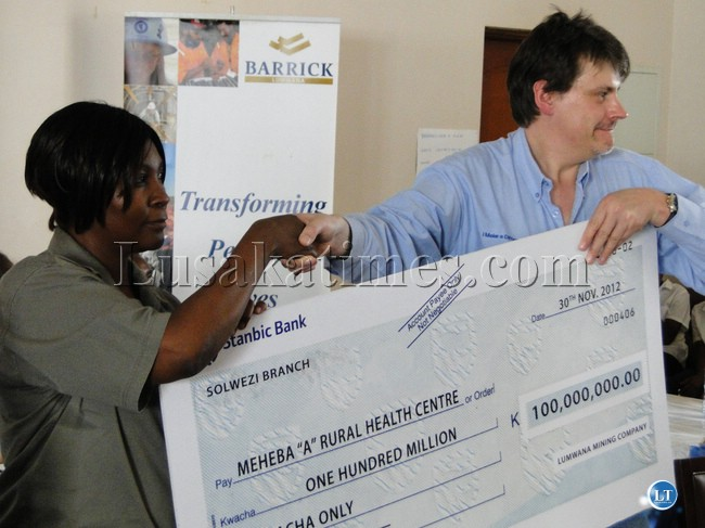 Barrick Lumwana acting managing director Guy Cordingley (right) and a Ministry of Health official display a cheque for K100 million donated to Meheba Rural Health Centre for the rehabilitation of the laboratory and purchase of equipment that supports CD4 count machine on the eve of the International Wolrd AIDS Day at Lumwana Pleasure Resort on Friday
