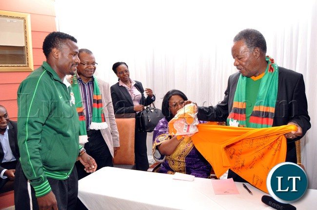 President Sata  and First Lady Dr Christine Kaseba  admires the Chipolopolo Jersey  presented to them by National Team Captain Christopher Katongo