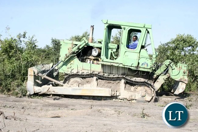 Zambia National Service (ZNS) Caterpillar operator clearing the area for the new ultra Mongu Stadium shortly after the launch