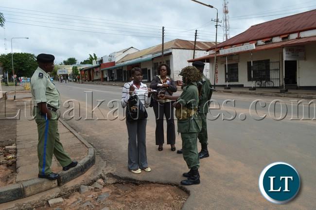 Police Officers check the identity cards of Zambezi FM reporters Angela Hanunka (far right) and Kawewa Kabika (middle) outside court premises in Livingstone