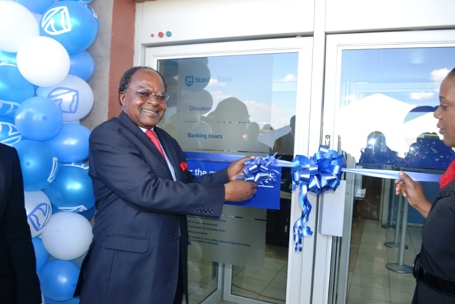 BANK of Zambia governor Michael Gondwe cuts the ribbon during the  launch of   Stanbic Zambia Bank Chisokone Market Trader Branch