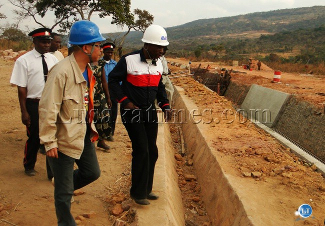 NORTHERN Provincial Minister Obious Chisala (right) inspecting a water canal at Lunzuwa Hydro-Power station in Mpulungu district yesterday with China National Electric Engineering Company (CNEEC)'s Assistant Manager Cheng Yu Hong in a blue helmet.