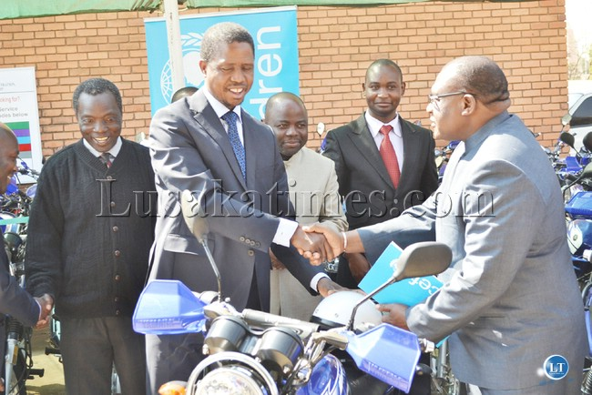 Home Affairs Minister Edgar Lungu shakes hands with UNICEF representative Iyorlumun Uhaa after receiving 70 motorbikes donated by UNICEF to the Department of National Registration Passport and Citizenship in Lusaka