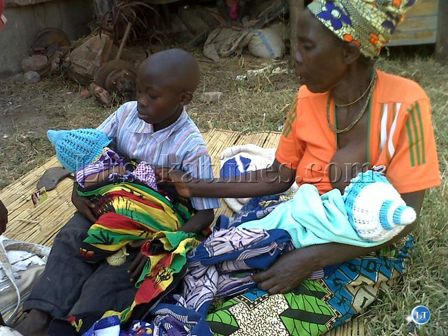 File:Ms Christine Chisha forced to breastfeed her orphaned grandson as his twin sister waits for her turn in the arms of cousin.