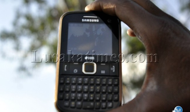 A resident of Mandevu using a mobile phone
