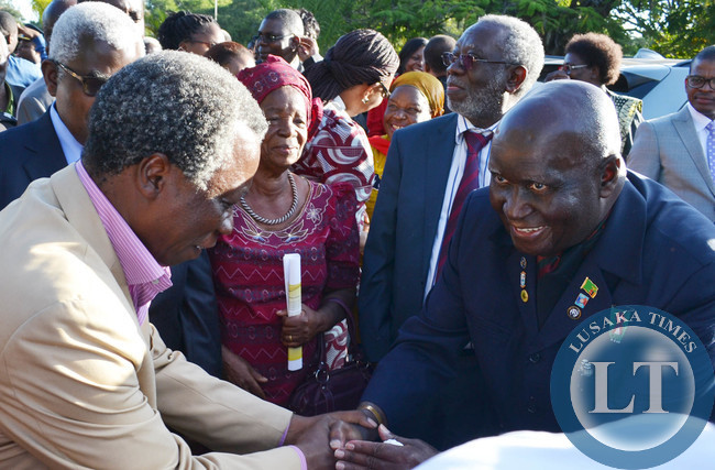 First Republican President Kenneth Kaunda shakes hands with opposition People's Party leader Mike Mulongoti at Cathedral of the Holy Cross in Lusaka