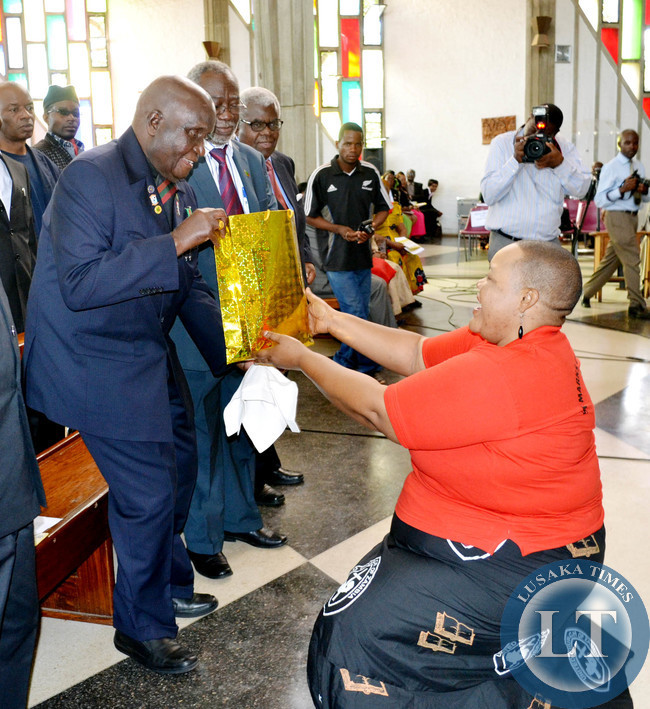 Dr Kaunda receives a birthday present during a church service to commemorate his 90th birthday at Cathedral of the Holy Cross in Lusaka