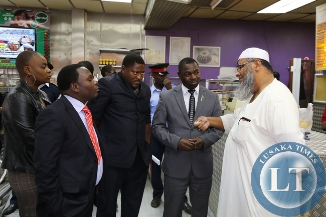 Lusaka Province Permanent Secretary Wamunyima Muwana listens to LA Fast Foods Managing Director Ahmed Patel while Lusaka DC Arshwel Kampengele and Lusaka Province DPS Bright Nundwe looks on during an on the spot check at LA Fast Foods Long Acres