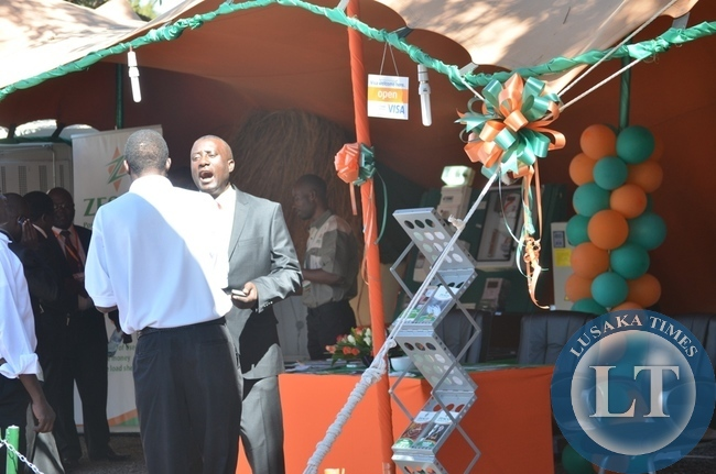 ZESCO spokesperson Henry Kapata (right) talks to a client at his firm's pavilion yesterday during the ongoing eighth Southern Tourism, Agricultural and Commercial Show Society (STACSS) in Livingstone