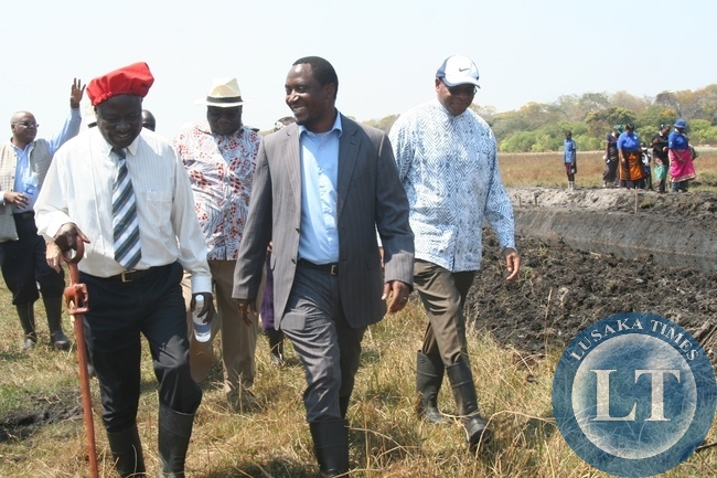 Western Province Minister Richwell Siamunene (c), World Bank Group Executive Director Dr. Denny Kalyalya (r) and Barotse Royal Establishment (BRE) Induna Inete Akapelwa Silumbu (l) walking on the banks of the 20 kilometre Natonga Canal during the visit of the Zambia Strengthening Climate Resilience Project in the Barotse Sub-Basin in Imalyo area of Mongu District
