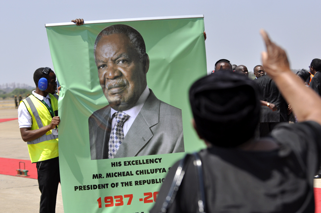An unidentified relative to the first family mourning Sata in front of the late president's placard