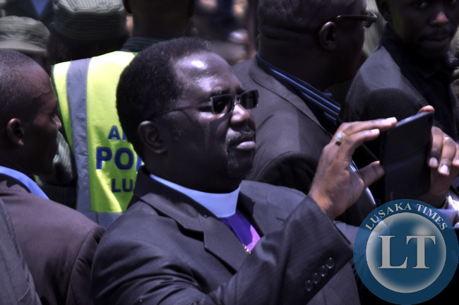 Bishop Joe Imakando takes photographs of the proceedings after Sata's body arrived