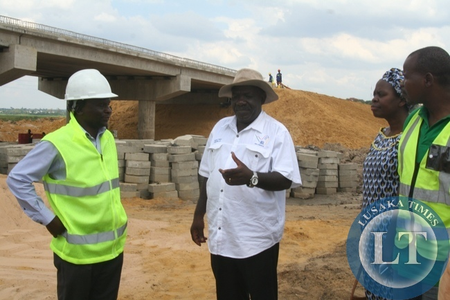 Cabinet Office Permanent Secretary for Special Duties Bert Mushala (c)flanked by Road Development Agency (RDA) Western Province Regional Manager Gershom Mwagomba (l) and Mongu District acting Commissioner Alice Mutemwa(r) inspecting the construction progress of Mongu-Kalabo Road Project during the tour in Western Province to compile major developmental projects