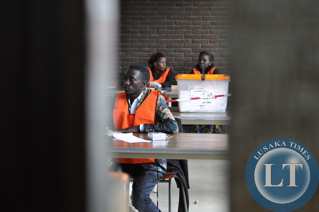 Polling officers wait for voters inside the City Library Polling Centre in Lusaka