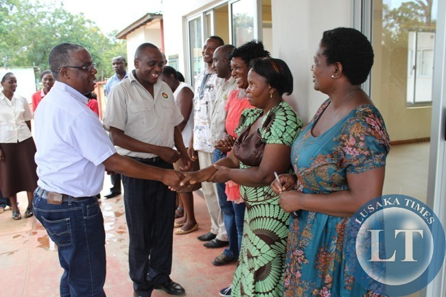 Southern Province Minister (left) Mr. Nathaniel Mubukwanu greets some civil servants in Monze as Monze District Commissioner Mr. Biggie Mwiinde makes introductions. The Minister was recently on a tour of developmental projects in the District.