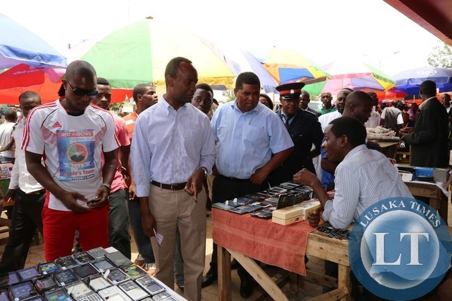 State house Deputy Minister Mulenga Sata (c) flanked by Lusaka Province Minister Obvious Mwaliteta talks to a phone vendor Jacob chelo at Lusaka town center