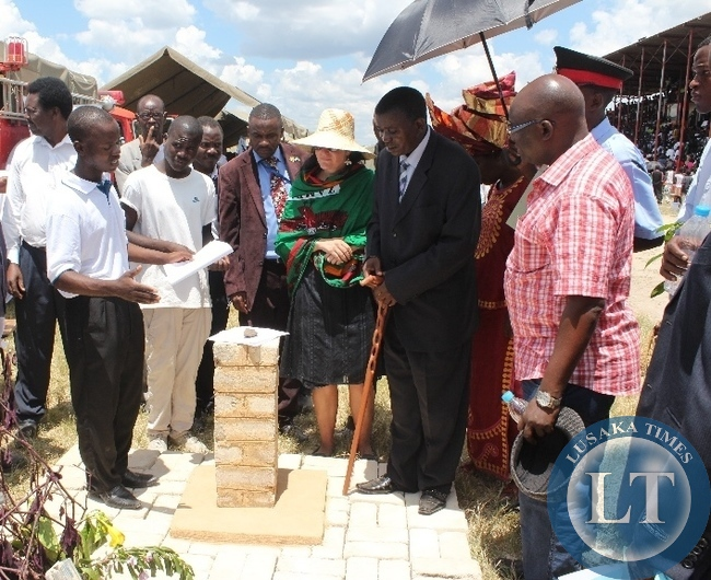 Mongu Trades training Institute 2nd year Brick laying student DerrickSitali (l) demonstrates the skills he has obtained to Western Province Permanent Secretary MwangalaLiomba (r) and Youth Expo Technical Committee Chairperson Lucie Hrabcova (c) during the tour of Youth Expo Stands at the commemoration of Youth Day at Mongu Stadium in Western Province