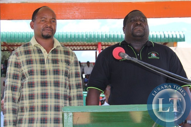 INFORMATION and Broadcasting Minister Chishimba Kambwili (r) and Choma Central Member of Parliament Conelius Mweetwa stand together as matchers (not in picture) pass. This was during the Youth Day celebrations at Choma stadium