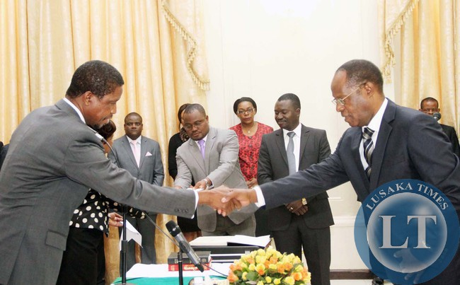 President Edgar Lungu congratultaes Newly appointed Chiefs and Traditional affairs Permanent Secretary Bernard Pwete (r) during the Swearing-In-Ceremony at State House on April 22,2015 -Picture by THOMAS NSAMA