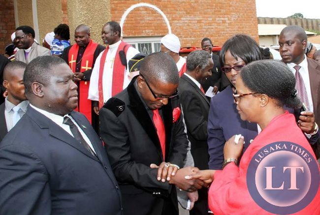 Cozmo Mumba greets First Lady Esther Lungu during the funeral sevice of Late Rev Sampa Bredt at St Pauls UCZ Church as Works, Supply, Transport and Communucations Minister Yamfwa Mukanga  looks on on April 10,2015 -Picture by THOMAS NSAMA