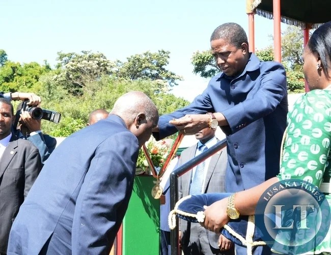 President Edgar Lungu giving a golden jubilee medal to the first President Kenneth kaunda during the investiture ceremony at State House