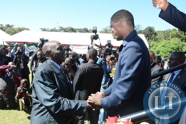 President Edgar Lungu shakes hands with first Local Government and Housing Minister Sikota Wina during the investiture ceremony at State House