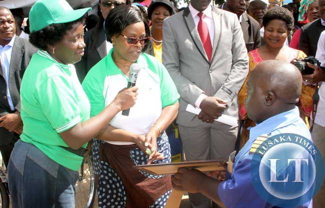 First Lady Esther Lungu presents an award  to Mazhandu Family Bus representative Chanda Beu  during the Commemorations of the International Day of Families  in Kapiri Mposhi on May 15,2015 -Picture by THOMAS NSAMA