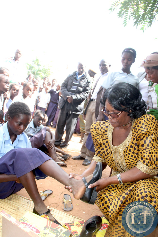 First Lady Esther Lungu helps one of  Chiweza Primary School pupils  Brian Mumba wear the shoes she donated to them in Hofmeir area on May 19,2015. The First Lady is in Eastern Province for the Outreach programme for People with Special Needs