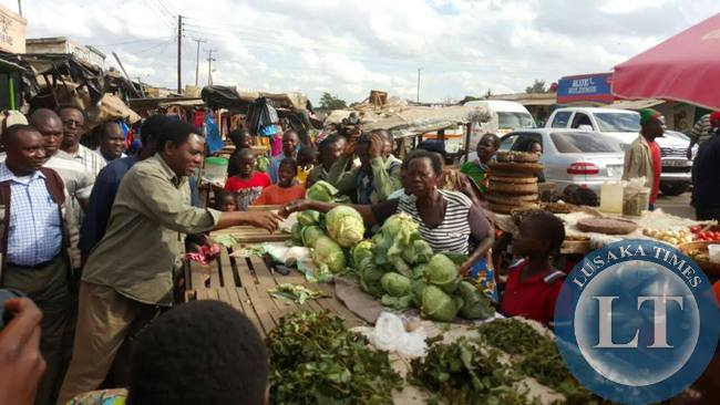UPND president Hakainde Hichilema buys from a trader at a local market
