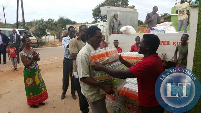 UPND President Hakainde Hichilema  helps offload soft drinks in Linda compound