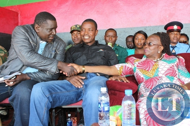 Community Development Minister Emerine Kabanshi (r) shakes hands with Zambia Congress of Trade Union (ZCTU) Vice President Newman Bubala (l) after delivering his speech as Western Province Minister Poniso Njeulu (c) looks on during Labour Day Celebrations at Mongu Stadium in Mongu on Friday.