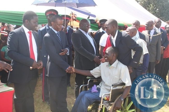 Chiefs and Traditional affairs minister Dr Joseph Katema  (second left) congratulates Emmanuel Samu, a typist from culture department for being the most hard working during 2015 labour day celebrations at Youth Alive grounds in Solwezi on Friday. Looking on the left is senior labour officer Charles Muwowo.