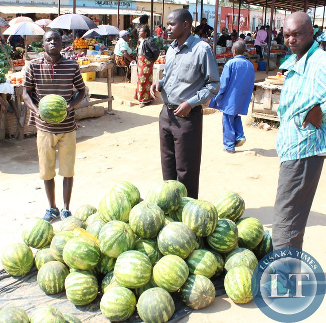 A trader at Serenje Market lures customers to buy his water melons