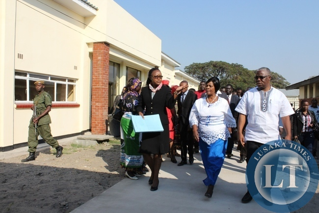 Lewanika General Hospital Superintendent Dr. Mapani Mutanga (l) leads First Lady Esther Lungu (c) and Mongu Central MP Nathanael Mubukwanu (r) through the tour of the hospital during the commissioning of a relatives' shelter constructed with the support of the Ministers' Wives Club in Mongu