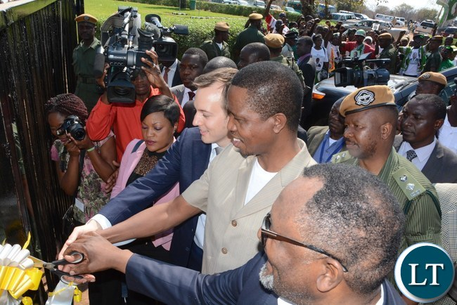 President Edgar Lungu (c) cuts the ribbon and is being helped to cut by the Chairman of the board Adam Taylor (l) and The Director of Yalelo Zambian Fish Fisho Mwale