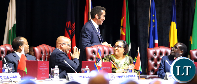 President Lt. Gen. Seretse Khama Ian Khama of Botswana (Incoming SADC Chairperson, standing) shares a light moment with President Robert Mugabe of Zimbabwe (Outgoing SADC Chairperson ) during the official opening of the 35th Ordinary Summit of Heads of State and Government in Gaborone, Botswana on Monday, August 17th 2015. Picture by EDDIE MWANALEZA/STATE HOUSE