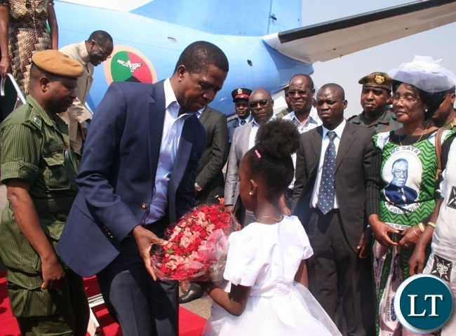 President Edgar Lungu receives a bouquet of flowers from a nine year old girl Sante Mwanza upon arrival at Solwezi airport as provincial Patriotic Front (PF) women' chairlady Martha Mpila ( r) looks on in Solwezi