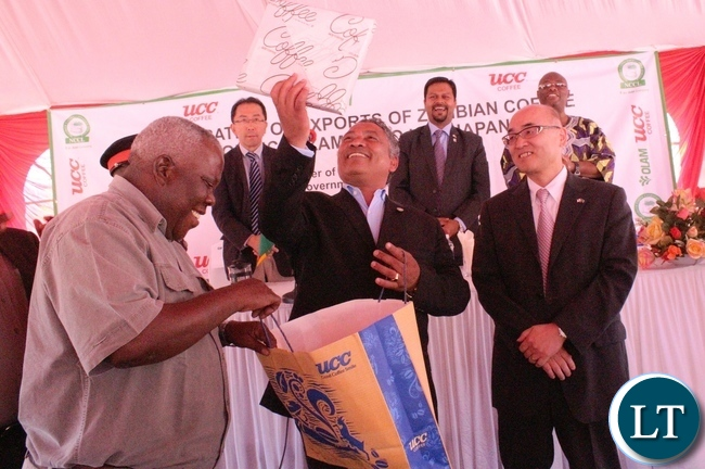 Minister of Agriculture Given Lubinda listens with UCCI Representative Tetsuya Seki after the inauguration ceremony of the shipping of the coffee beans to Japan produced by Olam Limited today.Looking on is northern Province Minister Freedom Sikazwe. Picture by Mary Bwembya.