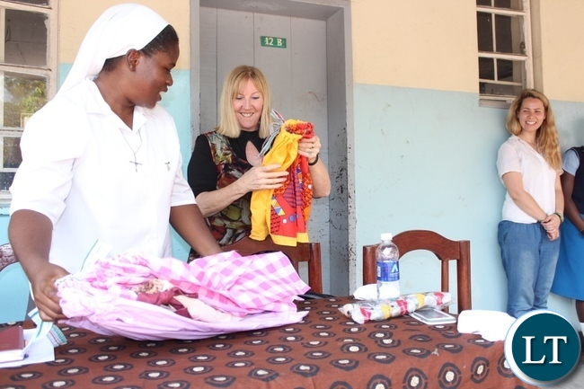 Holy Cross Girls Secondary School Manager Bibian Mbao (l) receives some clothes from Dignity Zambia CEO Sandy Clark (c) as Australian Music Teacher Cate Dyer (r) looks on during the donation of assorted items to the school in Mongu