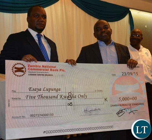 Deputy Minister of Commerce and Trade Miles Sampa(l) presents the dummy cheque of five thousand kwacha to a logo competition winner Esaya Lupunga(r) during the Zambia Bureau of Standards launch of the new logo at hotel intercontinental