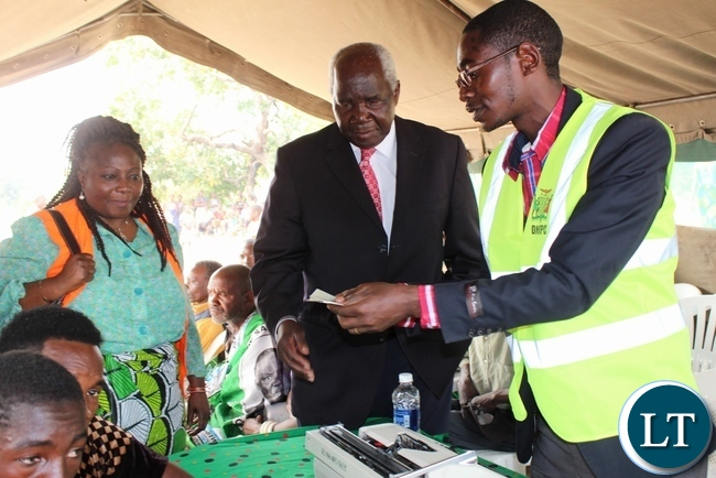 Deputy Minister of Home Affairs Col. Panji Kaunda (c) checking from Mongu District Registrar Chilumbwe Davison that everything is correct on the NRC before issuing it as Deputy Chief Passport and Citizenship Officer Alice Mwape (r) looks on during the launch of Phase II of the 2015-2016 Mobile National Registration Card Exercise in Nalolo District, Western Province
