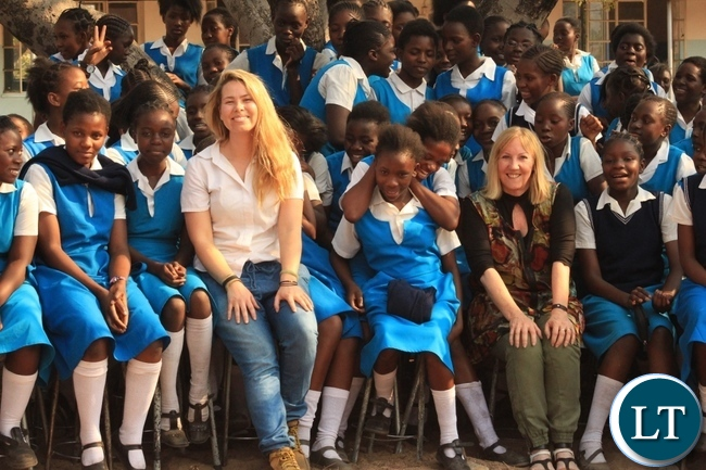 Dignity Zambia CEO Sandy Clark (r) and Australian Music Teacher Cate Dyer (l) in a group photo with Holy Cross Girls Secondary School pupils during the donation of assorted items to the school in Mongu