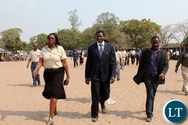 Education Deputy Minister David Mabumba (c) flanked by Western Province Assistant Secretary Sineva Kambenja (r) and Western Province Education Officer Loveness Mubisi (l) after touring the exhibition stands during the celebration of International Literacy Day at Mulambwa Primary School in Mongu