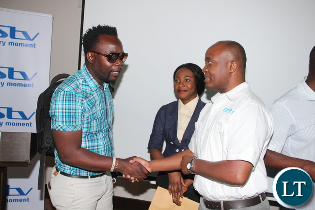 MultiChoice Zambia Public Relations Manager, Mwiika Malindima greets and shares a light moment with Music artist, Mweembe, formerly of the 'Black Muntu' fame