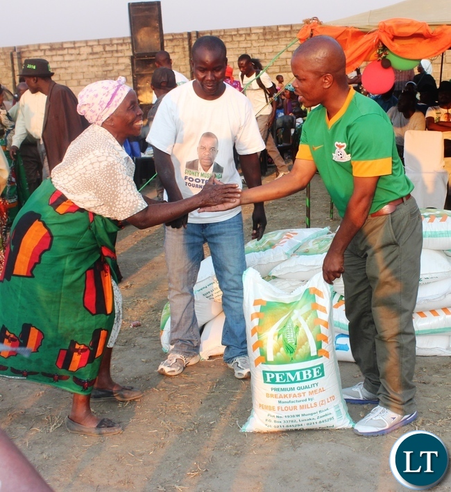 Education deputy Minister Sydney Mushanga (right) hands over a bag of mealie meal to one of the Zambian freedom fighters in Kabwe during the Sydney Mushanga sports tournament held in his constituency Bwacha recently.